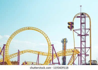 Roller coaster in amusement park as a background with blue sky and copy space