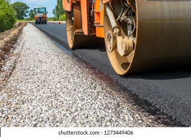 roller compacts asphalt on the road during the construction of the road. compaction of the pavement in road construction. rink goes on fresh asphalt. roller wheel closeup. hard work.