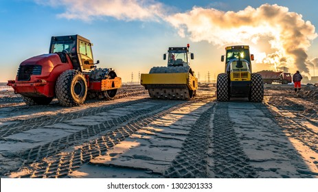 roller compacts soil in embankment on the road's construction. sand consolidation on road-building. Compactor driving on sandy. wheel marks on the sand. hard work. transportation of sand by trucks