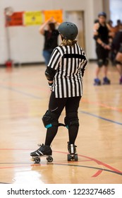 Roller derby referee watches teams for penalties