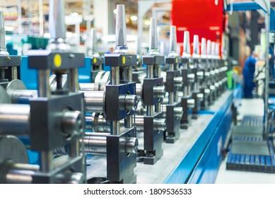 Walzenformmaschine. Das Innere der Anlage, die ein Metallprofil erzeugt. Blechbearbeitung.
