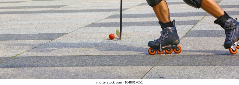 Roller in-line hockey outdoor. Closeup of two legs, the stick and the ball.