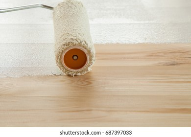Roller paints white paint a fresh wooden floor