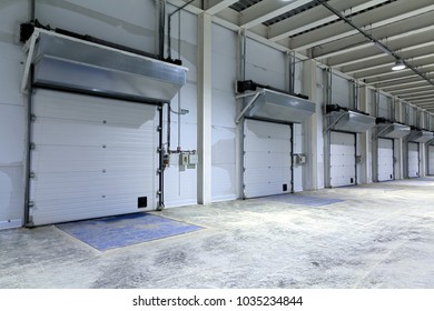 Roller shutter door and concrete floor inside factory building for industrial background.