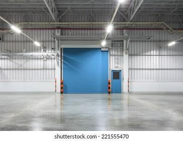 Roller shutter door and concrete floor inside factory building for industrial background.