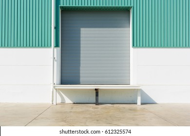 Roller shutter door and dock leveler ramp outside factory building for industrial background.