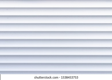 Roller shutter texture. Background with metal stripes in white. Iron roller shutters of white color. Abstract background for wallpaper in the form of straight lines.