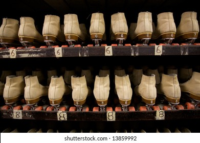 The roller skates are all lined up ready to be worn at the roller rink.