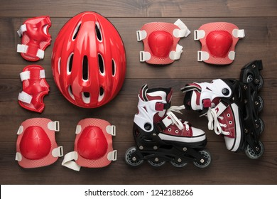 roller skates and body parts protection on brown table. top view of inline rollers, helmet, knee pads, wrist guards and elbow pads over wooden background
