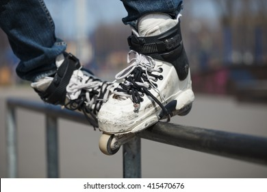 Rollerblader grinding on rail in skate park outdoors. Trick is top side soul or topsoul. Dangerous extreme skating popular among youth and teenagers.
