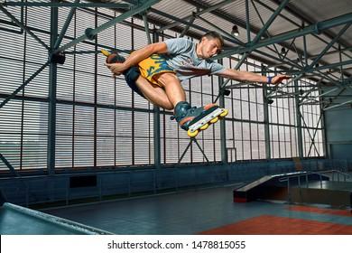 Rollerblader jump high from big air ramp performing trick. Indoors skate park equipment.
