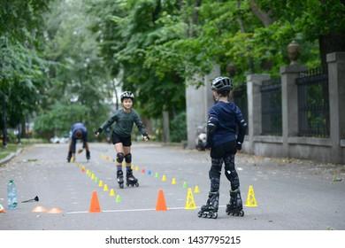 Rollerblading.Boys practicing in artistic slalom in a park. June 25, 2019. Kiev, Ukraine