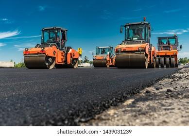 Roller rollen auf der neuen Straße frisch heißer Asphalt. Straßenbau.
