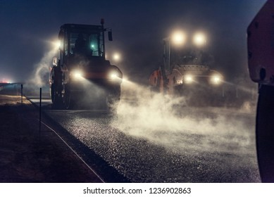 Nachts Asphalt mit Scheinwerfern rollen. Straßenbau.