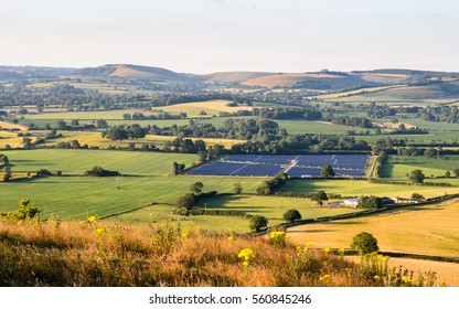 """Rolling chalk hills rise over agricultural fields and pasture in North Dorset's Blackmore Vale, the area of the Stour Valley known to Thomas Hardy as the """"vale of the little dairies""""."""
