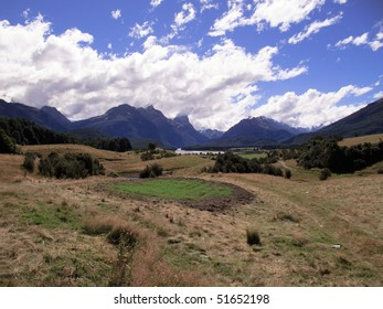 Rolling countryside valley in New Zealand with folded hills and mountains