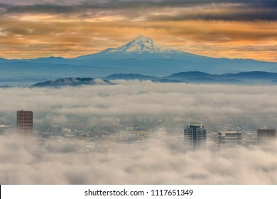 Rolling fog over the city of Portland Oregon downtown cityscape with Mount Hood during early morning sunrise