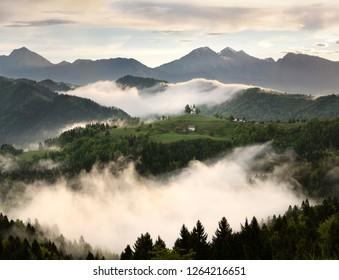 Rolling fog at sunrise with mountains of Kamnik Savinja Alps at Skofjelosko Hills with St Thomas church near Ljubljana Slovenia
