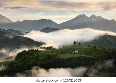 Rolling fog at sunrise in the Skofjelosko Hills with St Thomas church with mountains of Kamnik Savinja Alps near Ljubljana Slovenia