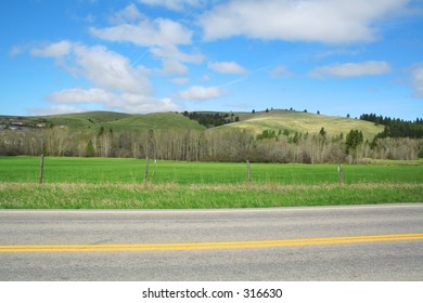Rolling hills and road against a bright blue sky.