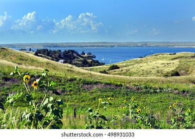 Rolling Nebraska grassland slopes down to blue, Lake McConaughy.  Tiny white sailboats dot small bay.