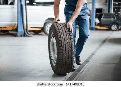 Rolling on the floor. Employee in the blue colored uniform works in the automobile salon.