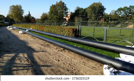 Rolling out pre-insulated heat pipes along a dirt road in a local community. EDE, THE NETHERLANDS -  OCTOBER 2019