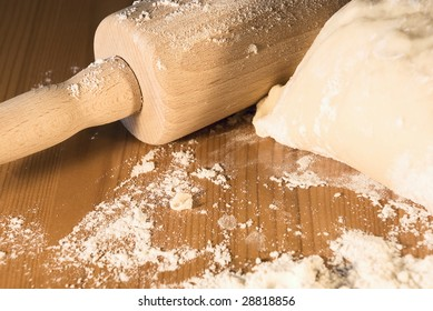 Rolling pin and the dough on a table with flour