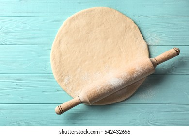 Rolling pin with dough  on wooden background