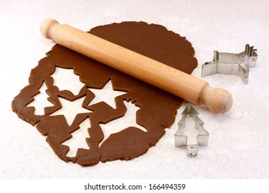Rolling pin and festive cookie cutters with gingerbread dough - reindeer, Christmas tree, star and holly leaf