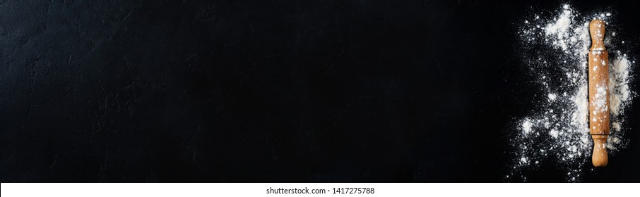 Rolling pin with flour on dark black baking background, top view, copy space for text, menu, recipe. Banner. Flat lay.