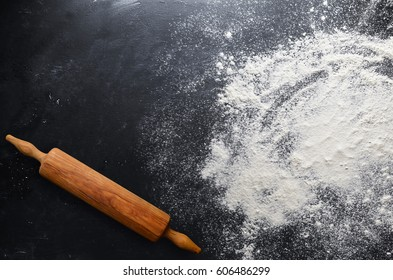 Rolling pin with flour on the table.