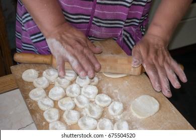 Rolling pin in hands to roll the dough for dumplings or pelmeni, vareniki or perogies on wooden kitchen desk.