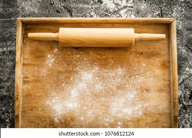 Rolling pin on empty pastry board sprinkled with flour. Kitchen scenery captured from above (top view, flat lay). Black chalkboard as background. Layout with free text (copy) space.