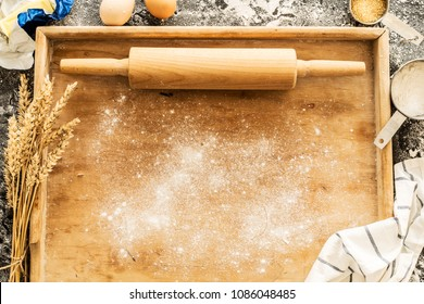 Rolling pin on pastry board sprinkled with flour, food ingredients around. Kitchen scenery captured from above (top view, flat lay). Black chalkboard as background. Layout with free text (copy) space.