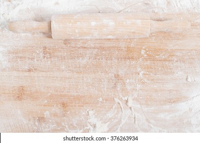 Rolling pin on a wooden tray covered with flour