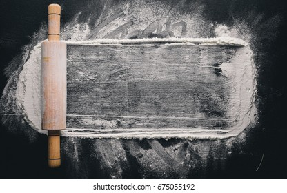 Rolling pin and white flour on a dark background. Free space for text . Top view.