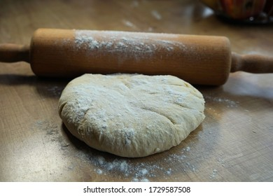 Rolling pin and yeast dough on the table