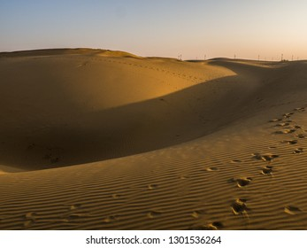 Rolling sand dunes of the Thar Desert in India, in the golden hour, not long after sunrise. A few footprints dotted over the sand, and wind turbines on the horizon in the distance