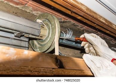 Rolling shutter repair. Worker adjusts a broken roller shutter of a home. Close-up of hands with gloves and orange starter screwdriver
