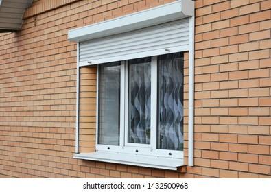 Rolling shutters brick house windows protection. Brick house with metal roller shutters on the windows