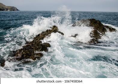 Rolling wave slamming on the rocks of the coastline
