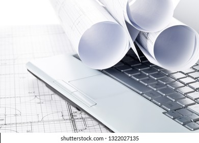 Rolls of architectural blueprint house building plans on laptop computer keyboard on blueprint background on table