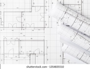 Rolls of architectural blueprint house building plans on blueprint background on table flatlay top view from above