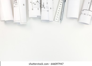 rolls with architectural plans, mechanic pencil and ruler on white background top view