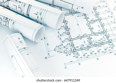 rolls of architecture blueprints with floor plan drawing on architects workplace