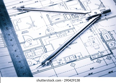 rolls of architecture blueprints and house plans on the table and drawing compass