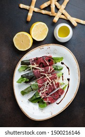 Rolls with carpaccio beef and salad leaves, flatlay on a dark brown metal background, vertical shot