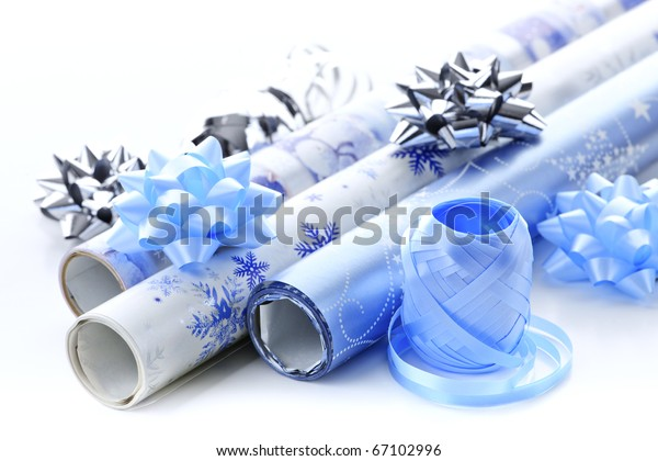 Rolls of Christmas wrapping paper with ribbons and bows