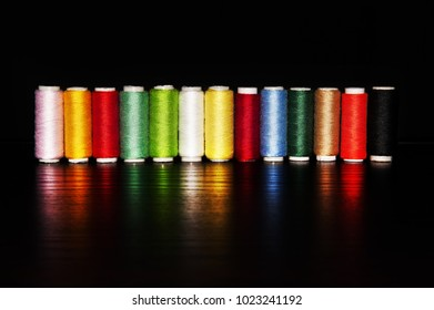 Rolls of colored cotton threads for hand and machine stitching.Isolated on black background with color reflection and arranged in a horizontal row.